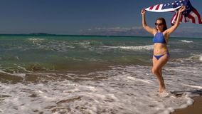 Beach bikini woman with US flag running along the water on the beach. Concept of Independence Day USA. Beach bikini woman with US flag running along the water on stock footage