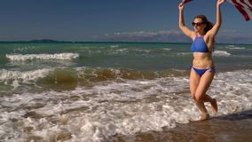 Beach bikini woman with US flag running along the water on the beach. Concept of Independence Day USA. Slow motion. Beach bikini woman with US flag running along stock footage