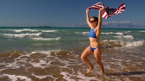 Beach bikini woman with US flag running along the water on the beach. Concept of Independence Day USA. Slow notion stock video footage