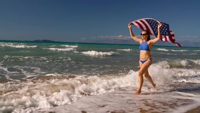 Beach bikini woman with US flag running along the water on the beach. Concept of Independence Day USA. Slow notion. Beach bikini woman with US flag running along stock video footage