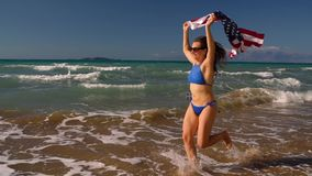Beach bikini woman with US flag running along the water on the beach. Concept of Independence Day USA. Beach bikini woman with US flag running along the water on stock video footage