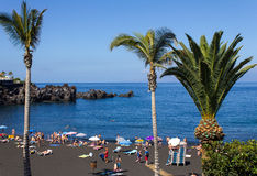 The beach with black volcanic sand and tourists. Stock Images