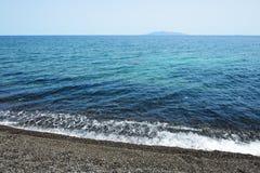 The beach with black volcanic stones at Santorini island Stock Photos