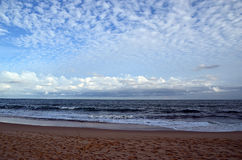 Beach and blue cloudy sky by the sea on sundown Stock Photos