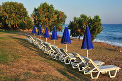 Beach with blue folded parasols Stock Photos