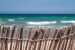 Beach: blue sea, sand and fence Royalty Free Stock Photography