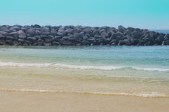 Beach with blue water and big stones Stock Photography