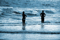 Beach Blues. Silhouette of 2 people in the water at the beach with blue hue Royalty Free Stock Photo