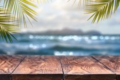 Beach blurred background with palm leaves background with vintage old wood table. Landscape view with old wood table top and coconut leaf over blurred blue sea royalty free stock photography