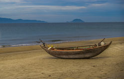 Beach Boat. Island fishing boat sitting up on beach with blue ocean and sky background Stock Images