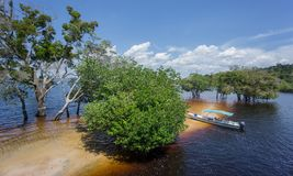 Beach and boat in the middle of Rio Negro, Brazil Royalty Free Stock Images
