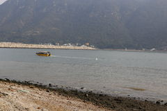 Beach and boat. Taken from beach in tai o Hong Kong. Mountain behind, boat on sea, gravel in foreground Stock Images