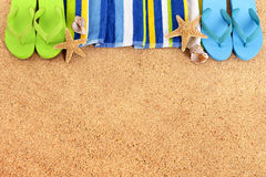 Beach border, flip flops, sand background, copy space. Beach background border with flip flops, towel, starfish and seashells. Copy space royalty free stock photo