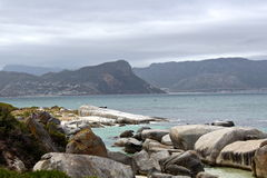 Beach boulders with mountain background. A secluded, romantic, and peaceful beach with blue water, white boulders, and distant mountains in Simons Town, South royalty free stock photo