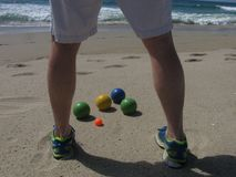 On a sunny California beach, a bocce player stands in front of the balls, planning his next move. stock images