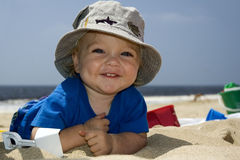 Beach Boy. Small boy  smiling on the beach with hat and beach toys Royalty Free Stock Image