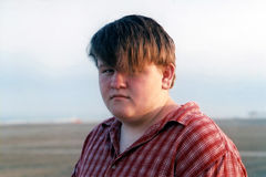 Beach Boy. Portrait of a teenage boy with the ocean and beach in the background stock photography