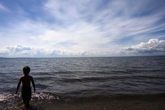 Beach boy. Silhouette of a boy standing in the water at the beach Stock Photo