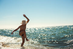 Beach boy dancing having fun backlight littered horizon Royalty Free Stock Images