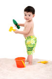 Beach Boy Toddler With Toys In The Sand. Toddler boy in swim suit playing in the sand.  Shot in studio with the Canon 20D Stock Photo