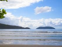 Beach and sea with waves, and island in the background. Beach in Brazil on sunny day and sea with waves, forest island in the background and clouds in the sky Stock Photography