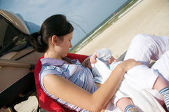 Beach breast feeding. Mother breast feeding her newborn on the beach by pram stock photos