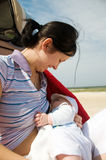 Beach breast feeding fun. Mother breast feeding her newborn on the beach by pram royalty free stock photography