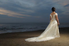 Beach Bride. Beautiful Asian woman in wedding dress on the beach, looking away over the sea. Dramatic lighting Royalty Free Stock Photography