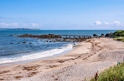 Beach and bridge at Ballycastle, Northern Ireland. Sand beach with small wooden bridge at Pan's Rock near Ballycastle in County Antrim and far view of royalty free stock photos