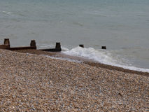 On the beach. Brown stones, gray water, surf breakers stock photography