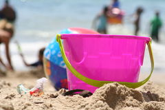 Beach Bucket. Bright pink beach bucket sitting on the sand Royalty Free Stock Photo