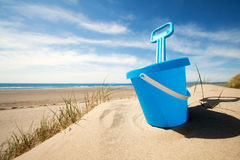 Beach bucket and spade. Childs bucket and spade or sand pail and shovel at the beach on a sunny summer day royalty free stock photos