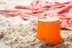 Beach bucket tiy and towel on beach sand Royalty Free Stock Photos