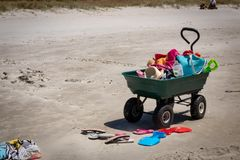 Beach buggy wheelbarrow, sandals, and sand sculpture tools, Matarangi Beach, New Zealand. Beach buggy wheel barrow with equipment for annual summer sand royalty free stock photography