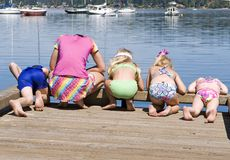 Beach Bums. Five children bend over to view the sea life below the docks royalty free stock photography