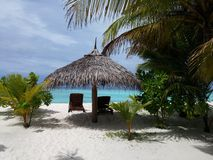 Beach. Bungalow with deck-chair on the ocean Royalty Free Stock Photo