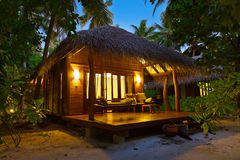 Beach bungalow at sunset - Maldives Stock Photo