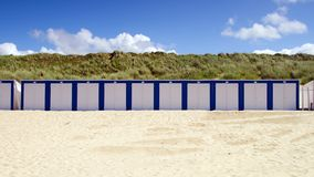Beach Cabins in White and Blue. Wooden cabins on a sunny blue sky beach in blue and white royalty free stock photo