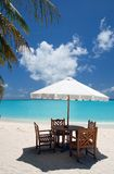Beach Cafe. Dining place with wooden chairs, table and white sun shade in a cafe on an maldivan island in the Indian Ocean Royalty Free Stock Photo