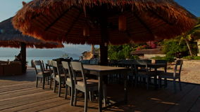Beach Cafe with Tables Chairs Reed Umbrellas against Sea stock video