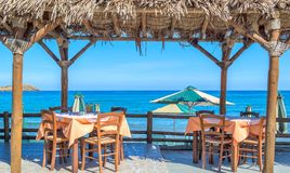 Beach cafe with wooden tables and chairs at the sea Royalty Free Stock Photos