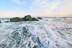 Beach and calm sea at sunset. Beach at sunset (sunrise) beautiful sky with clouds. waves run ashore, taken on a long exposure, the ripples on the water and foam Stock Photography