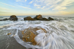 Beach and calm sea at sunset. Beach at sunset (sunrise) beautiful sky with clouds. waves run ashore, taken on a long exposure, the ripples on the water and foam Royalty Free Stock Photos
