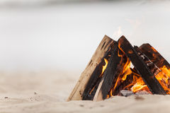 Beach campfire on lake with sand shore. Royalty Free Stock Photos