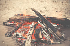Beach campfire on lake with sand shore. burning wood on white sa Stock Photo