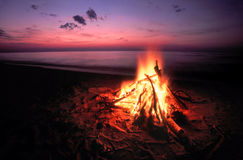 Beach Campfire on Lake Superior. Blazing campfire at sunset along the beautiful beach of Lake Superior in northern Michigan Royalty Free Stock Image