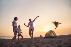 Beach Camping. Family camping and activity on the beach at sunset. Mother and child flying kite at beach Stock Photo