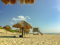 Beach in Cancun, Mexico with straw umbrellas royalty free stock photography