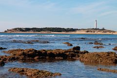 Beach of the Canos de Meca, with the lighthouse of Trafalgar in the background, in the cape of the same name, in the south of Spai. Beach of the Caños de Meca stock photo