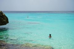 snorkeling girl looking at the crystal clear blue sea stock photography